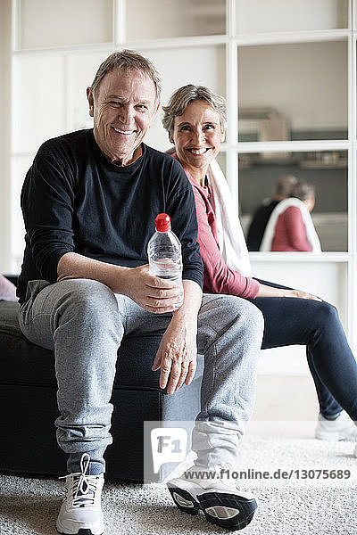 Portrait of sporty couple sitting on sofa at home