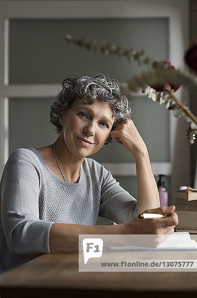 Portrait of mature female writing in book at home