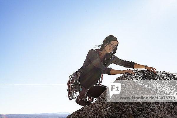 Frau klettert an einem sonnigen Tag gegen den Himmel