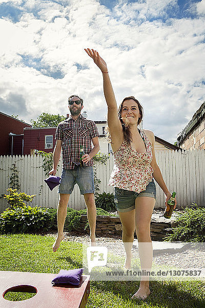 Glückliches Paar beim Bohnensack-Wurfspiel auf dem Rasen
