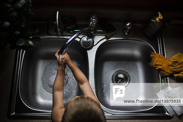 High angle view of boy washing hands in kitchen sink at home