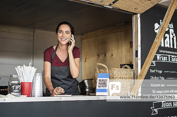 Portrait of smiling female vendor talking on smart phone while working in food truck