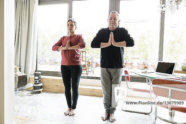 Relaxed senior couple practicing yoga at home