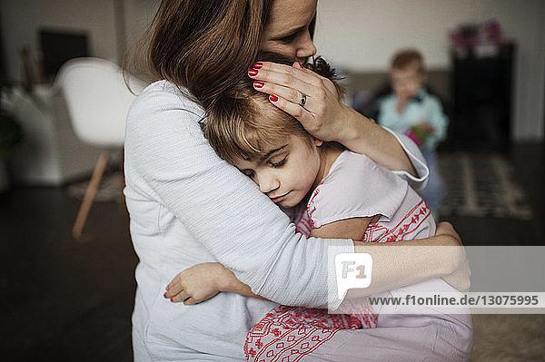 Mutter umarmt Mädchen  während sie zu Hause auf dem Boden sitzt
