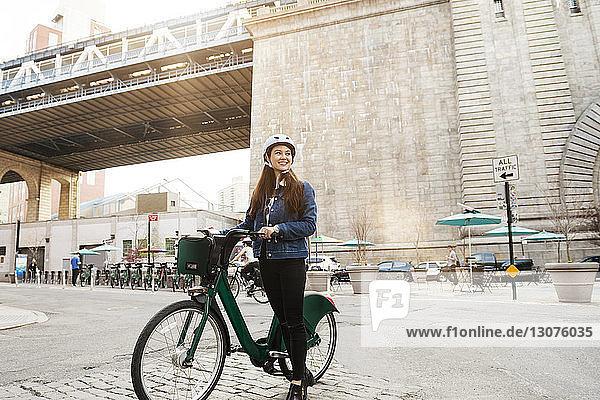 Frau mit Fahrrad auf Stadtstraße gegen Brücke