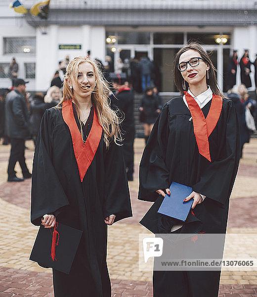 Porträt von glücklichen Studentinnen in Abschlussroben  die gegen das Gebäude stehen
