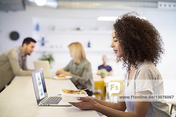 Geschäftsleute  die Laptop-Computer beim Mittagessen am Tisch benutzen