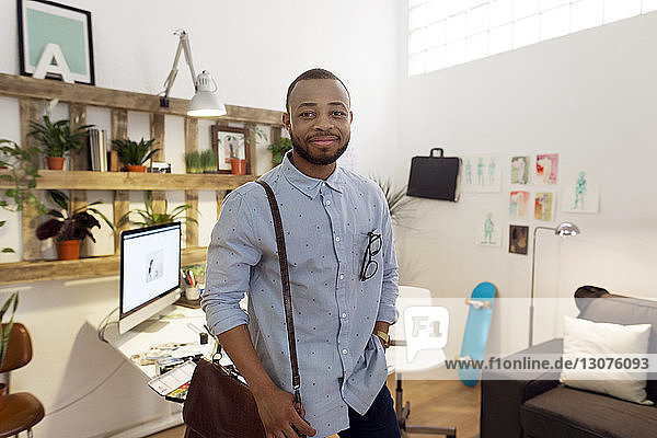 Portrait of smiling male illustrator carrying bag while standing in creative office