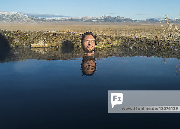 Man with eyes closed in calm lake against sky