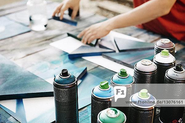 Hochwinkelansicht einer Frau  die Kunstwerke auf dem Tisch arrangiert