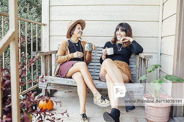 Freundinnen bei einem Drink auf einer Holzbank in der Veranda sitzend