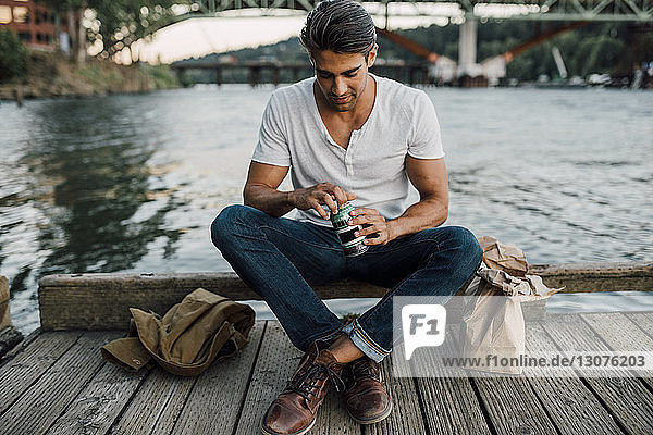 Man opening drink can while sitting on pier over river during sunset
