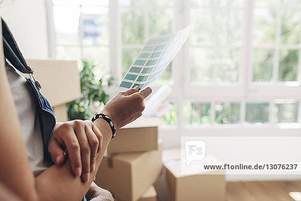 Midsection of woman holding color swatch while standing at new home