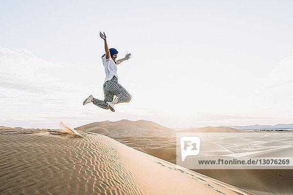 Happy woman jumping at Merzouga desert against sky