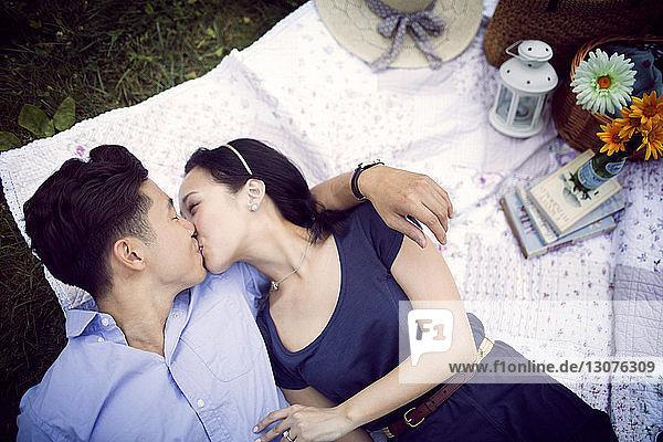 Draufsicht auf ein Paar  das sich küsst  während es auf dem Spielfeld im Park liegt