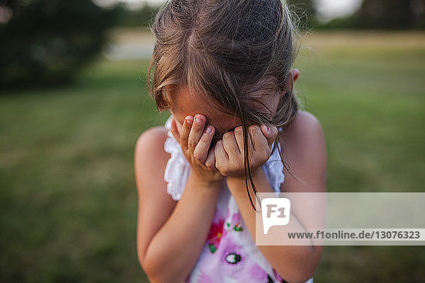 Close-up of girl covering face while crying outdoors