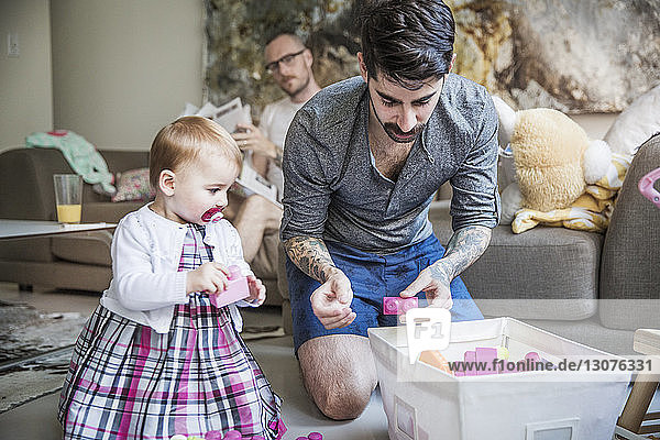 Gay man playing with daughter with partner reading newspaper in background