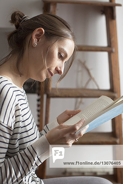 Close-up of woman reading book while sitting at home