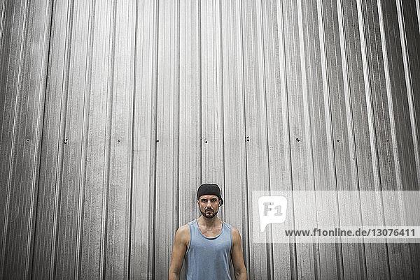 Serious man standing against metallic wall