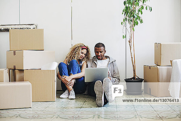 Couple using laptop computer while sitting on floor at new house