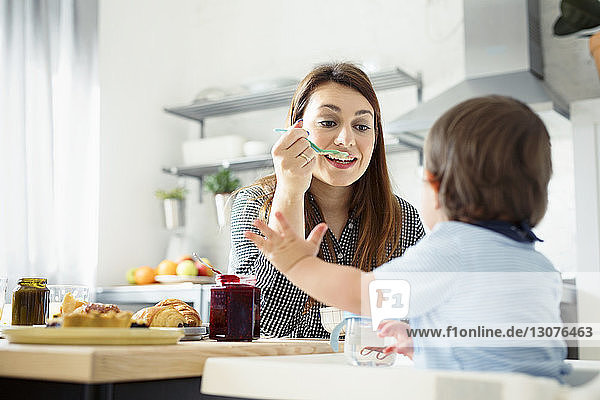 Mother feeding breakfast to son at table in kitchen