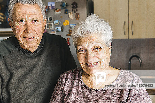 Porträt eines älteren Ehepaares  das zu Hause in der Küche steht