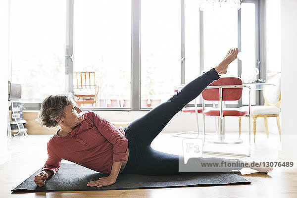 Determined mature woman exercising on floor at home