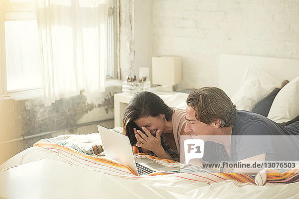 Couple using laptop computer while lying on bed at home