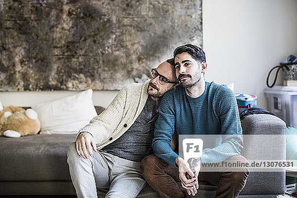 Loving homosexual couple sitting on sofa at home