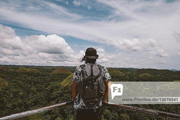 Rückansicht eines Mannes mit Rucksack beim Blick auf Chocolate Hills  der am Geländer steht