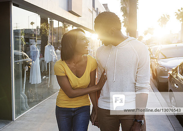 Glückliches Paar hält sich bei Sonnenschein beim Gehen auf dem Bürgersteig an den Händen