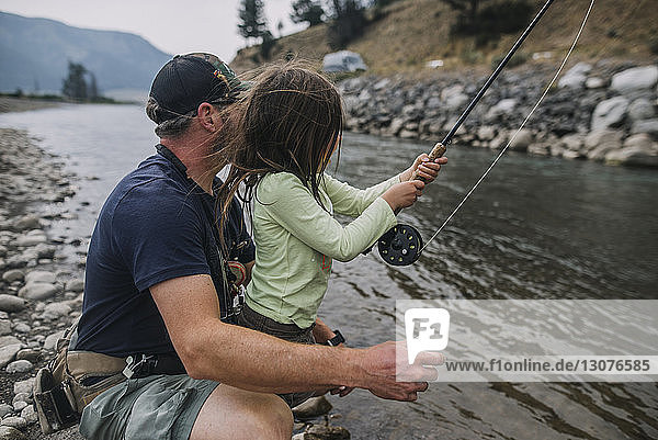 Side view of father and daughter fishing in river at Yellowstone National Park