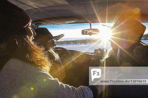 Freundinnen  die im Winter an sonnigen Tagen im Auto sitzen