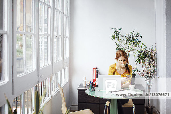 Businesswoman using phone while sitting at table with laptop in office