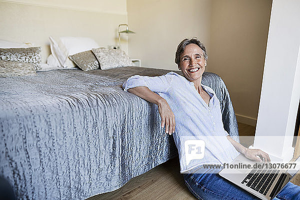 Portrait of happy mature woman sitting with laptop on floor in bedroom