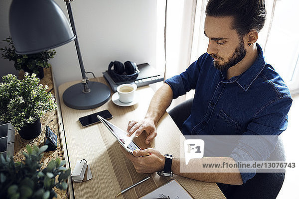 High angle view of man using tablet computer while sitting at table