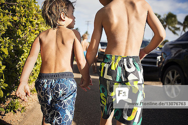 Two boys walking along cars