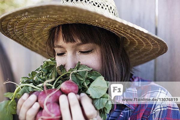 Junge Frau riecht Radieschen auf Bio-Bauernhof