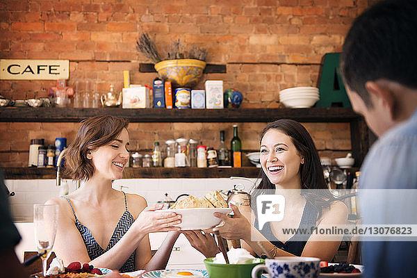 Frau serviert Freundin bei Tisch Brot gegen Küchentheke