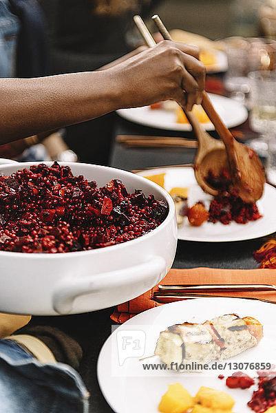 Ausgeschnittenes Bild einer Frau  die Essen serviert  während sie am Tisch sitzt