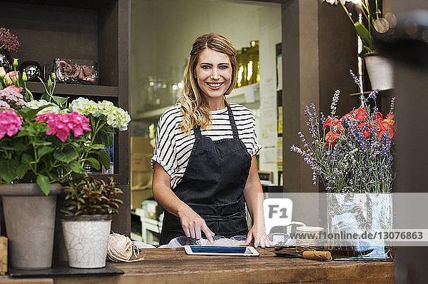 Porträt eines lächelnden Floristen mit Tablet-Computer im Geschäft