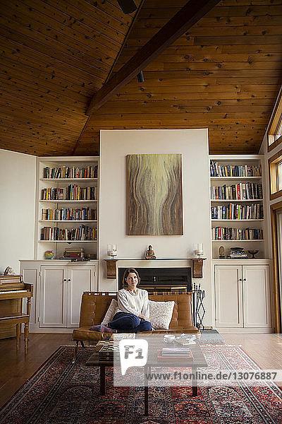 Nachdenkliche Frau sitzt auf Stuhl gegen Regale im Wohnzimmer