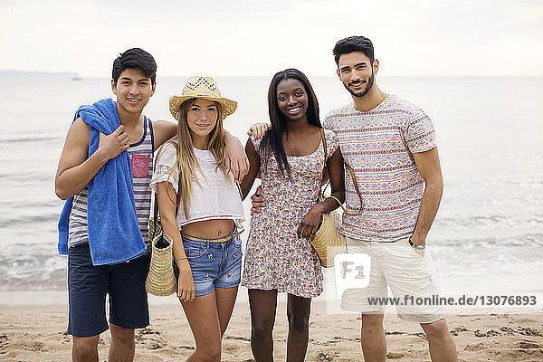 Portrait of happy multi-ethnic friends standing on beach