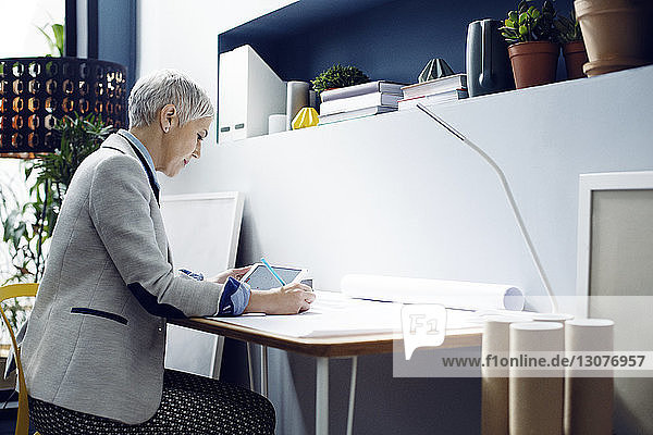 Female architect working while using tablet in office