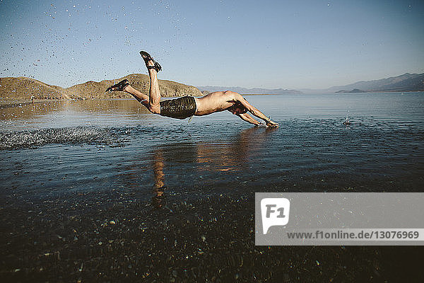 Seitenansicht eines Mannes ohne Hemd  der bei klarem Himmel in den See springt