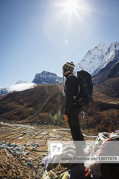 Hiker with backpack standing on mountain against clear blue sky during sunny day