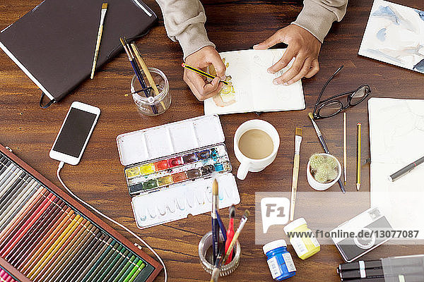 Cropped image of male illustrator making painting at desk in creative office