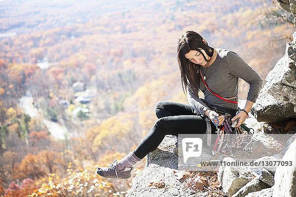 Frau betrachtet Kletterausrüstung  während sie am Fels sitzt