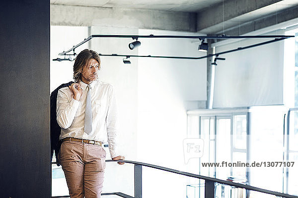 Mature businessman looking away while standing by railing at office