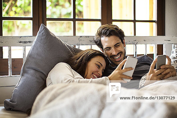 Happy couple using smart phones while lying on bed at home